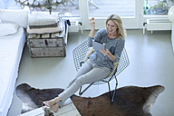 Smiling blond woman using digital tablet at home - MAEF009998