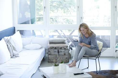 Smiling blond woman using digital tablet at home - MAEF009999