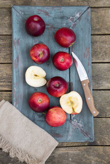 Red apples, knife and place mat on dark wood - SARF001582