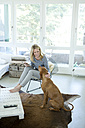 Woman with her dog and digital tablet at home - MAEF010013