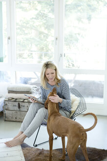 Woman with her dog and digital tablet at home - MAEF010014