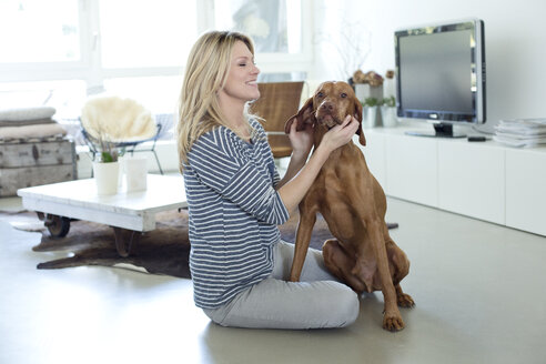 Woman playing with her dog at home - MAEF010016