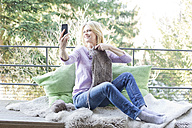 Blond woman sitting on balcony taking a selfie with her knitting - MAEF010055