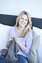 Portrait of blond woman sitting on couch knitting - MAEF010034