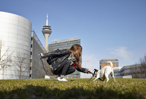 Germany, Dusseldorf, Young woman playing with her dog - RHF000654