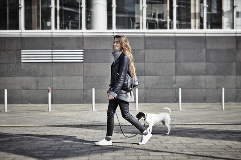 Germany, Dusseldorf, Young woman walking her dog - RHF000663