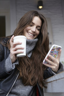 Germany, Dusseldorf, Young woman with coffee cup using smart phone - RHF000681