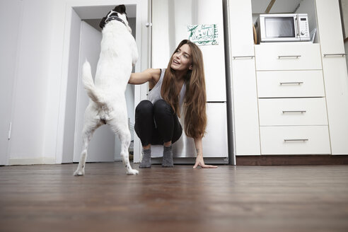 Young woman in kitchen playing with dog - RHF000684
