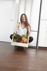 Happy young woman in kitchen with crate full of fresh vegetables - RHF000691
