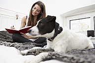 Young woman sitting on bed with dog writing diary - RHF000700