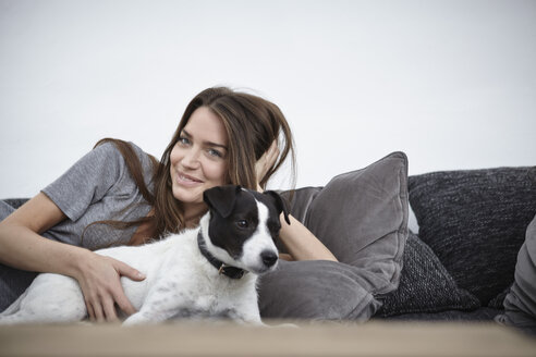 Young woman relaxing with dog on couch - RHF000713