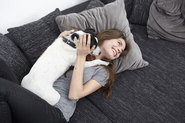 Young woman playing with dog on couch - RHF000716