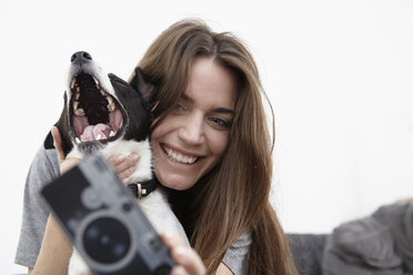 Young woman taking selfie with dog - RHF000746