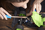 Young woman repairing toy car - RHF000729