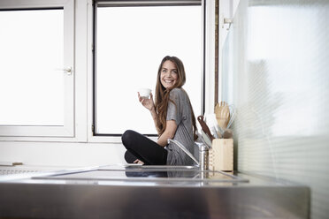 Young woman in kitchen sitting at window drinking coffee - RHF000737