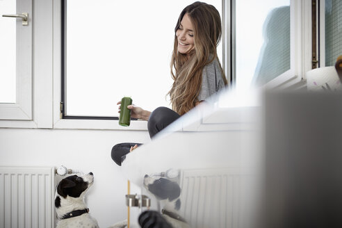 Young woman in kitchen sitting at window, smiling at dog - RHF000748