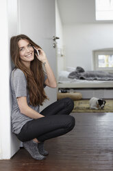 Young woman with dog at home on the phone - RHF000749