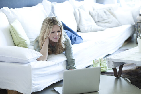 Woman relaxing on couch using laptop - MAEF010054