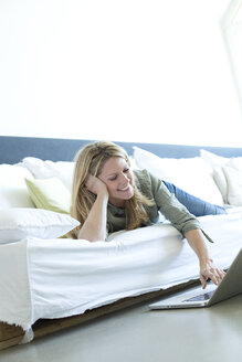 Woman relaxing on couch using laptop - MAEF010059