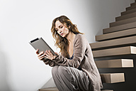 Woman sitting on floating staircase looking at digital tablet - PDF000909