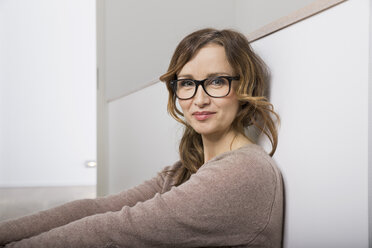 Portrait of smiling woman with glasses leaning against wall - PDF000903