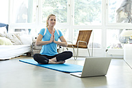 Woman with laptop practicing yoga on gym mat in living room - MAEF010092