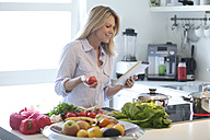 Woman with digital tablet cooking in kitchen - MAEF010107