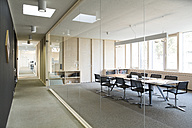 Corridor and modern conference room separated by glass pane - FKF000891