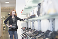 Smiling young woman in shoe shop - SGF001435