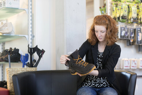 Young woman in shoe shop looking at hiking shoe - SGF001438