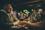 Smiling man sitting at counter of a pub - MBEF001369