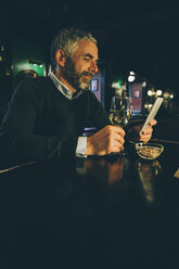 Smiling man sitting at counter of a pub using smartphone - MBEF001356