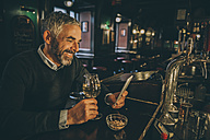 Portrait of smiling man sitting at counter of a pub using smartphone - MBEF001357