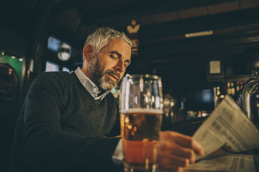 Man sitting at counter of a pub reading newspaper - MBEF001361
