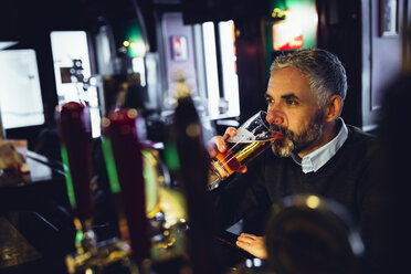 Man sitting at counter of a pub drinking beer - MBEF001373