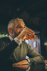 Man sitting at counter of a pub drinking beer - MBEF001366
