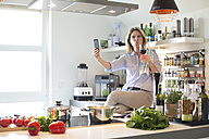 Woman in kitchen with glass of red wine taking a selfie - MAEF010127