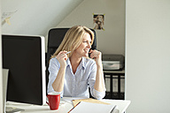 Smiling woman sitting at desk at home - MAEF010099