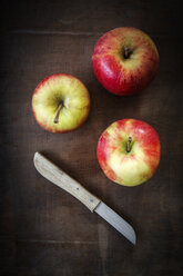 Three apples and kitchen knife on dark wood - EVG001572
