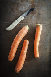 Three carrots and a kitchen knife on dark wood - EVG001582