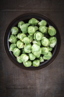 Bowl of Brussels sprouts on dark wood - EVG001587