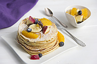Stack of mini pancakes filled with chocolate cream and sliced fruits - YFF000350