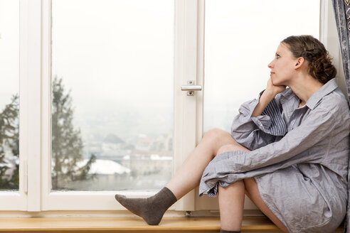 Woman in oversized shirt looking out of window - MIDF000227
