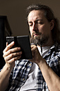 Man with braided beard looking at smartphone - MIDF000242