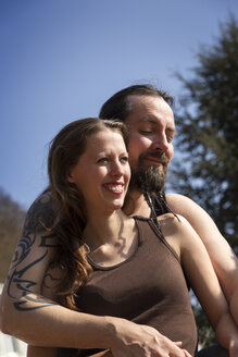Happy man and woman embracing outdoors - MIDF000255