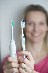 Woman holding classical and electric toothbrush - CHPF000128