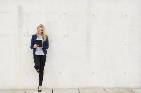 Smiling businesswoman with digital tablet leaning on concrete wall - BFRF001035