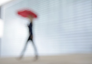 Businesswoman walking with red umbrella - BFRF001039