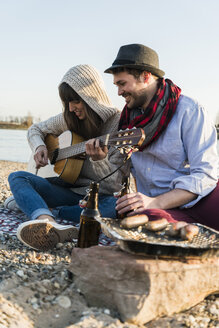 Couple sitting by the riverside, playing guitar - UUF003768
