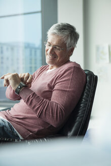 Smiling man sitting in a leather chair using smartwatch - RBF002575